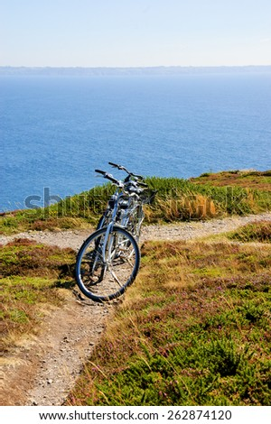 Two bicycles on the hill over the sea in sunny day. Breton coast near Cap de la Chevre. Brittany, France. Active summer vacation background. - stock photo