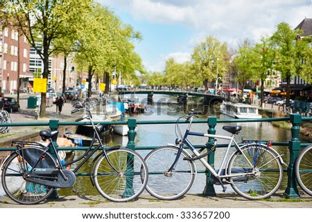 Two bicycles on the river channel bridge in Amsterdam
