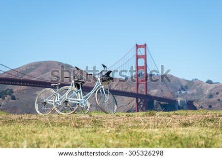 Two bicycles parked on grass in front of Golden Gate Bridge - stock photo
