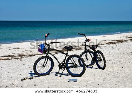 Two Bicycles with Baskets parked on the sandy beach of Anna Maria Island, Florida