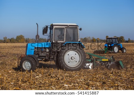 Two big blue tractor plowing a field and remove the remains of previously mown corn. The work of agricultural machinery. Harvest.