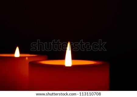 Two big burning candles, close up, on a black background. - stock photo