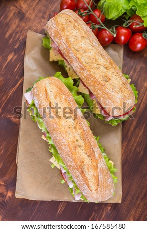 Two Big Ciabatta Sandwiches with lettuce, slices of fresh tomatoes, ham, turkey breast and cheese