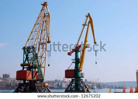 Two big cranes in seaport loading cargo