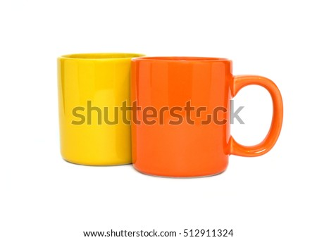Two big empty yellow and orange tea or coffee cups isolated on white background front view closeup