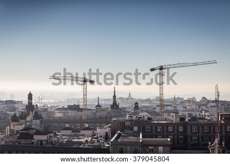 Two big hoisting cranes towering above the Madrid city centre rooftops in Spain