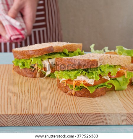 Two big sandwich on a kitchen table with a place for the object and male chef in the background. square frame