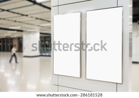 Two big vertical / portrait orientation blank billboard on modern white wall with blued passenger background - stock photo