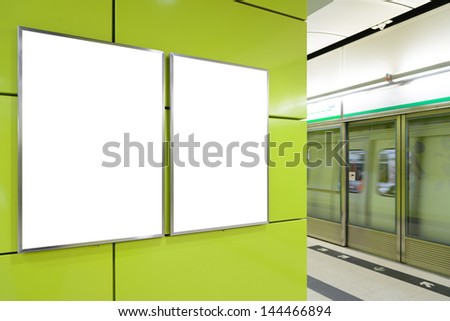 Two big vertical / portrait orientation blank billboard on yellow wall with train platform background - stock photo