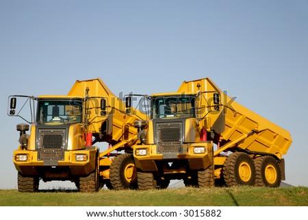 Two big yellow loading trucks standing outside - stock photo