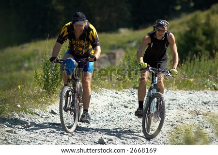 Two bikers on high mountain road - stock photo