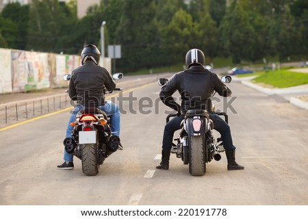 Two bikers ot motocycles handshaking with knuckle on road - stock photo