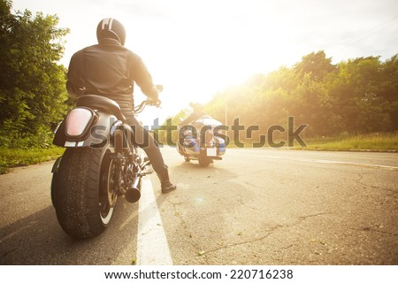 two bikers riding unknown motorbike with blur movement, speed concept - stock photo