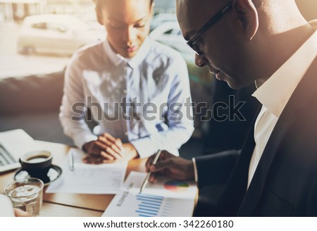 Two black business people discussing their business using charts to prove their success - stock photo
