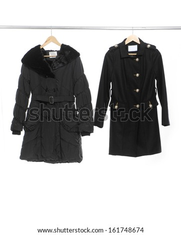 Two black coat clothes on a hanger - stock photo