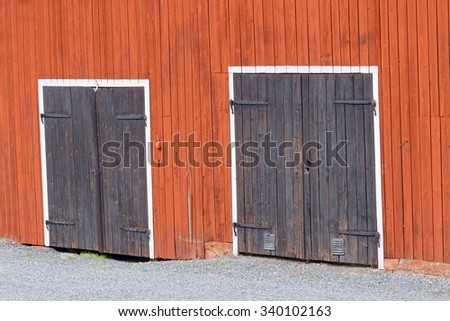 Two black doors with beautiful hinge in a red barn wall and white color around the door. Small pebbles in front of the doors