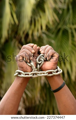 Two black hands of a young South African Xhosa man with big chain around the wrists in front of blurry green palm tree background.