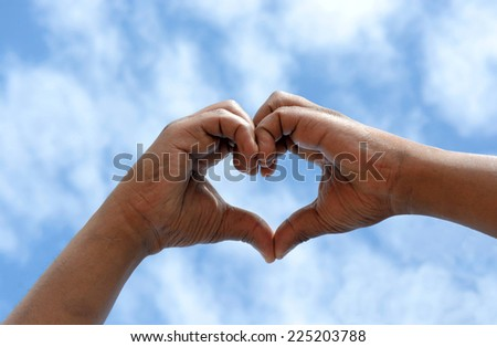 Two black hands of an African American man held together in a heart shape in front of blue sky background.