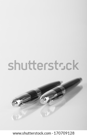 Two Black Luxury Metal Pens Isolated On White Reflective Background. Vertical Image