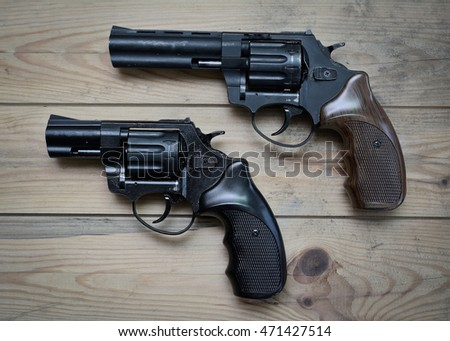two black revolvers on a wooden table