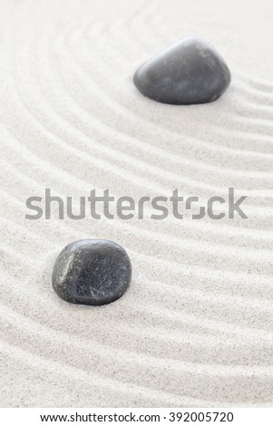 Two black stones in sand, spa or zen concept.
