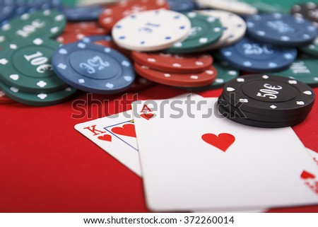 Two blackjack playing cards (the ace of hearts and the king of hearts)  and casino poker chips on red background - stock photo