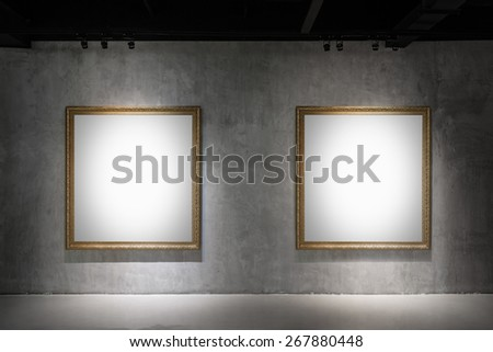 Two blank Antique golden frame on concrete wall in gallery room - stock photo