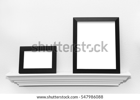 Two blank black picture frames on a picture display ledge attached to a wall