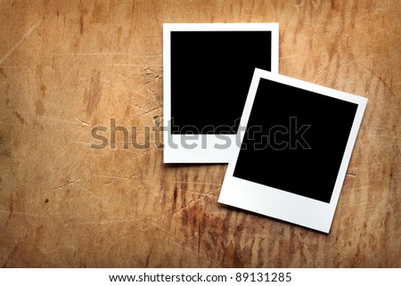 Two blank instant photo frames on old wooden background. - stock photo