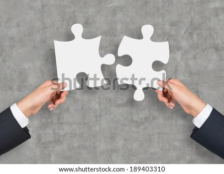 Two blank pieces of puzzle. Concrete wall. - stock photo