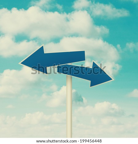 Two blank road signs pointing in opposite directions, blue sky background in vintage tone. - stock photo