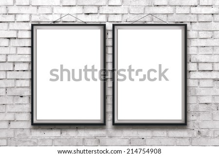 Two blank vertical painting or posters in black frame hanging on white brick wall. Painting proportions match international paper size A. - stock photo