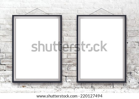 Two blank vertical painting poster in black frame hanging on white brick wall. Painting proportions match international paper size A. - stock photo