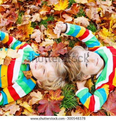 Two blond boys lying in autumn leaves in colorful clothing. Happy siblings having fun in autumn park on warm day. - stock photo