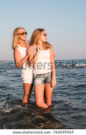 Two blond girls on the beach near sea or ocean. Mother and daughter have fun together