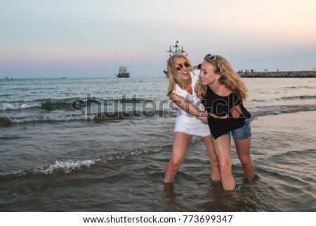 Two blond girls on the beach near sea or ocean. Mother and daughter have fun together in the evening during sunset
