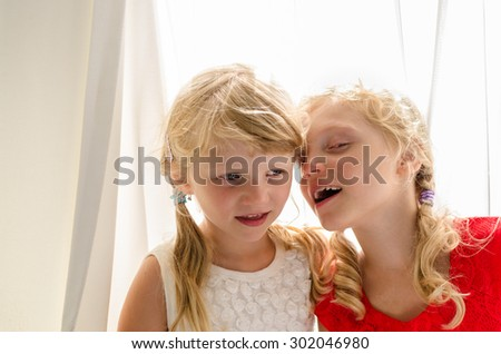 two blond girls with long hair gossiping together - stock photo