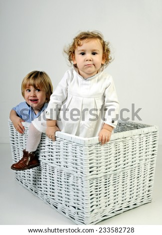 two blond infant kids playing in an enormous White straw laundry basket