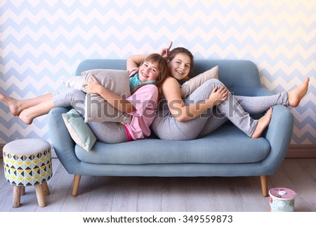 two blond teenager sisters in pajama with pillows in cozy bedroom interior with blue sofa and striped wallpapers