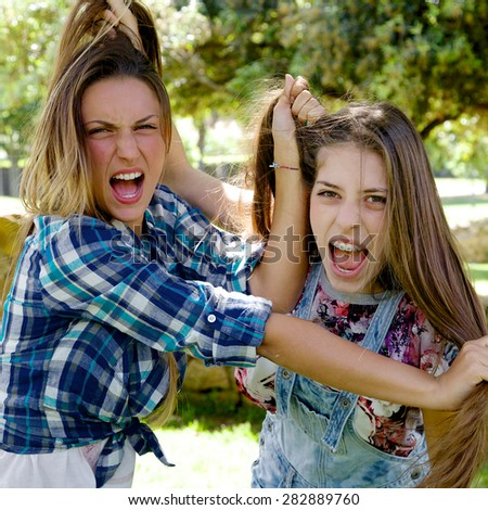 Two blond teenagers angry looking camera pulling hair fighting  - stock photo