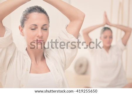 two blonde girl do yoga at gym