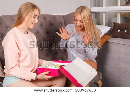 Two blonde woman on the sofa eating donuts