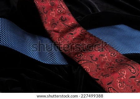 Two blue and red silk ties crossing on top of the other, while on display on black velvet - stock photo