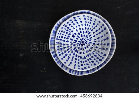 Two blue and white ceramic bowls on a black background
