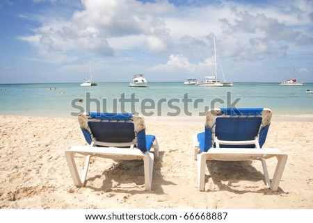 Two blue beach chairs on a tropical beach overlooking the ocean. - stock photo