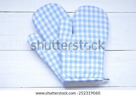 Two blue checkered oven gloves on an old white wooden table - stock photo