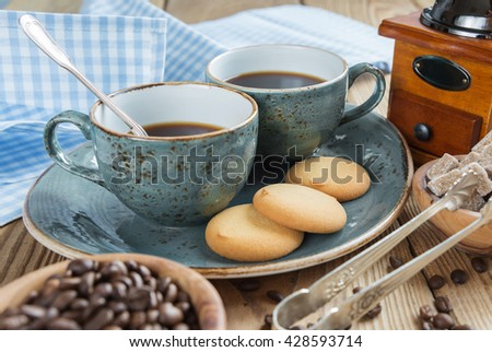 Two blue cups of black coffee, cookies and sugar pieces surrounded by checkered linen cloth and coffee beans on old wooden table - stock photo