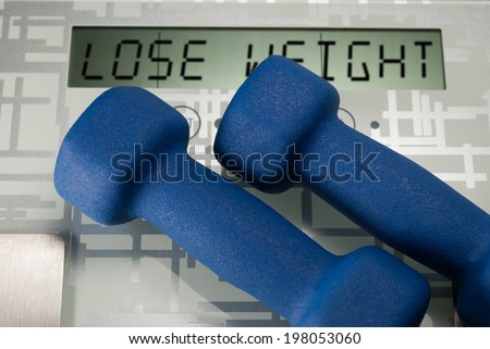 Two blue dumbbells on weighing machine with sign lose weight - stock photo