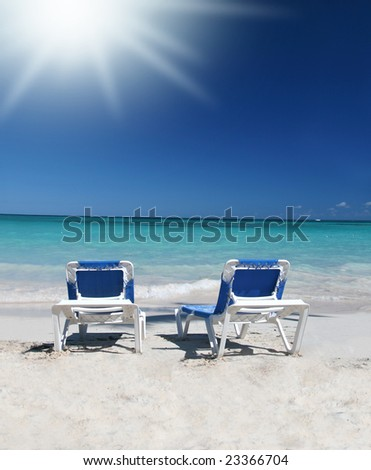 Two blue lounge chairs or beds on a beautiful Caribbean tropical beach with white sand and green ocean, suitable background for a variety of designs - stock photo