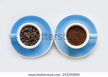 two blue macro coffee espresso cups with the fresh coffee beans and with a ground coffee on the white background - stock photo
